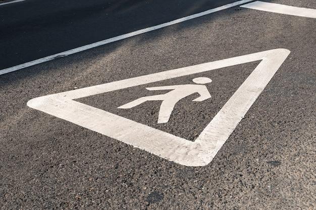 Znak dla pieszych namalowany na asfalcie drogi miejskiej. koncepcja przejścia dla pieszych
