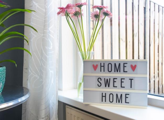 Znak domu słodki domowy tekst na lightbox, parapet w pobliżu okna z różowymi kwiatami, ozdobna ramka