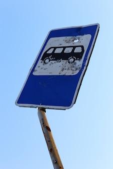 Znak drogowy do przystanku autobusowego na miejscu działań wojennych. dziury po kulach w metalu.