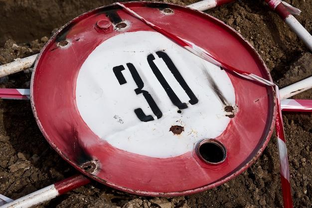 Znak drogowy informujący o ograniczeniu prędkości do trzydziestu kilometrów lub mil na godzinę oraz ogrodzenie drogowe do wykonywania prac naprawczych leży na ziemi