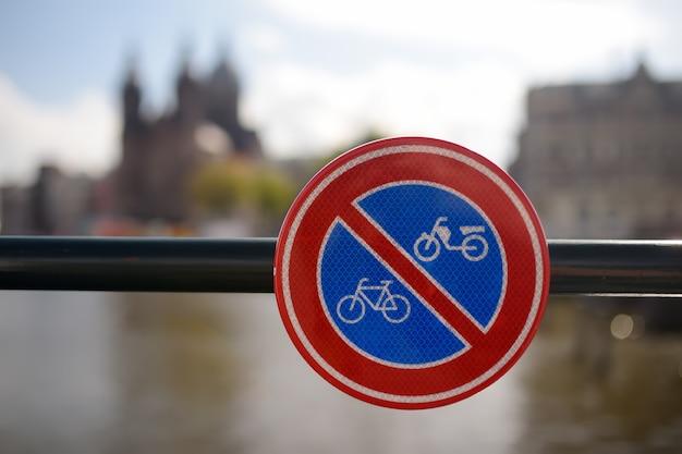 Znak drogowy na poręczy mostu w amsterdamie, holandia, zakazujący dostępu dla rowerów i motocykli. bezpieczeństwo na drogach.