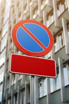 """Znak drogowy """"no parking"""" na nowoczesnym budynku. dwie puste biała tablica - miejsce na tekst."""