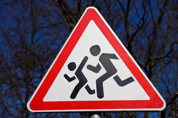 Znak drogowy ostrożne dzieci. ostrzeżenie kierowcy o biegnących ludziach. zdjęcie wysokiej jakości