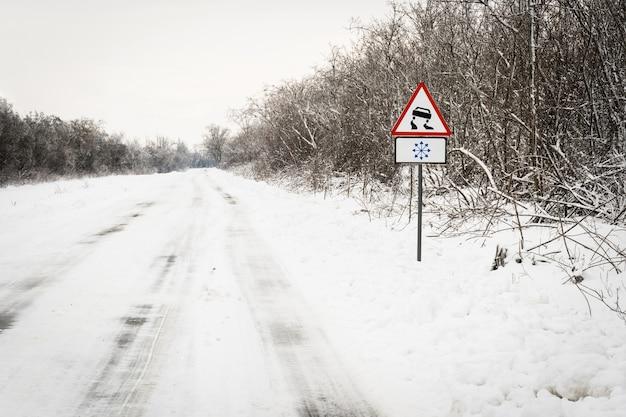 Znak drogowy ostrzega przed śliską drogą z powodu oblodzenia śniegu.