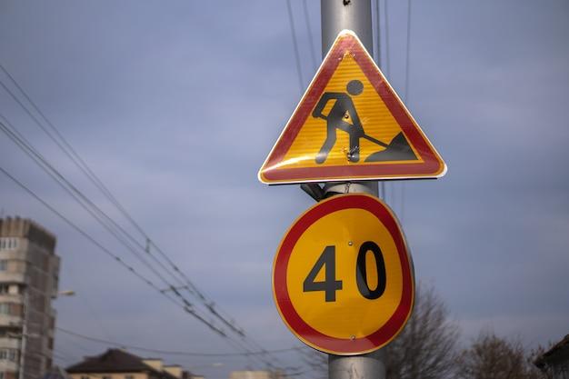 Znak drogowy ostrzegający o naprawie drogi i ograniczeniu prędkości
