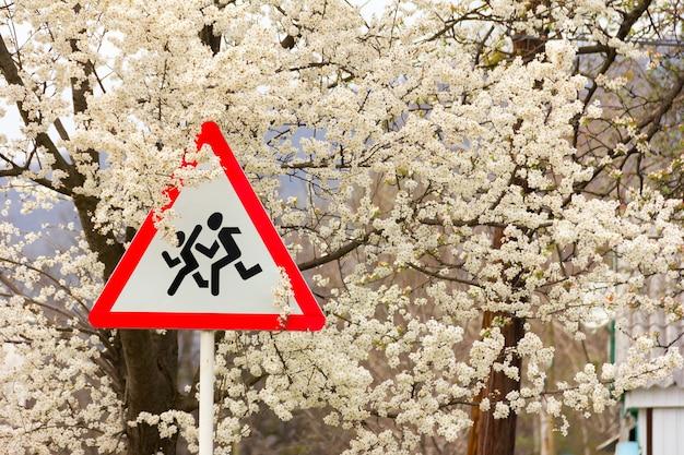 Znak drogowy ostrzegawczy - dzieci, na gałęziach kwitnącego drzewa owocowego. pojęcie bezpieczeństwa dzieci w ruchu drogowym.