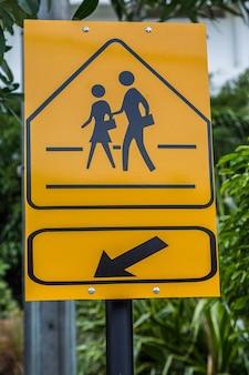 Znak drogowy szkolny znak ostrzegawczy tutaj z zielonym liścia tłem