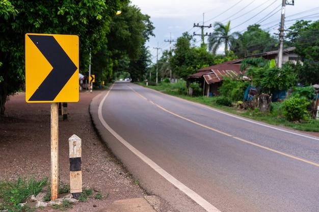 Znak drogowy umieszczony obok drogi na wsi, sygnał skręć w prawo