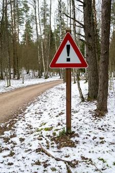 Znak drogowy w kształcie trójkąta z wykrzyknikiem na leśnej drodze