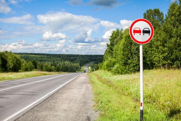 Znak drogowy wyprzedzanie jest zabronione na podmiejskiej autostradzie przez las w słoneczny letni dzień.