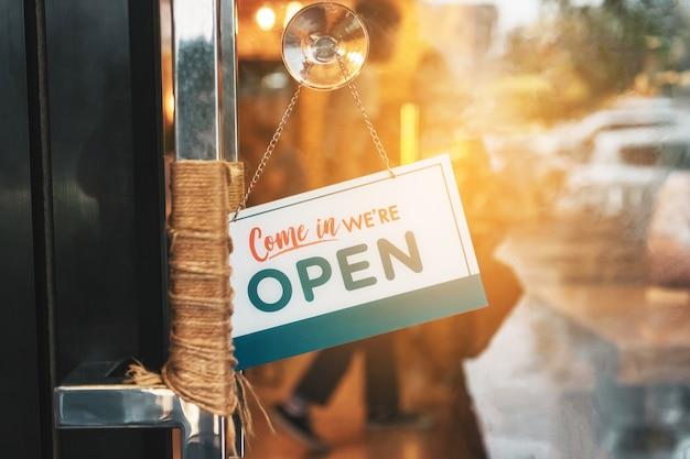 """Znak firmowy z napisem """"otwarte w kawiarni lub restauracji"""" wisi na drzwiach przy wejściu."""