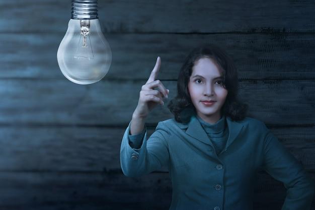 Znak godziny ziemi z azji kobieta biznesu i światła żarówki wyłączone