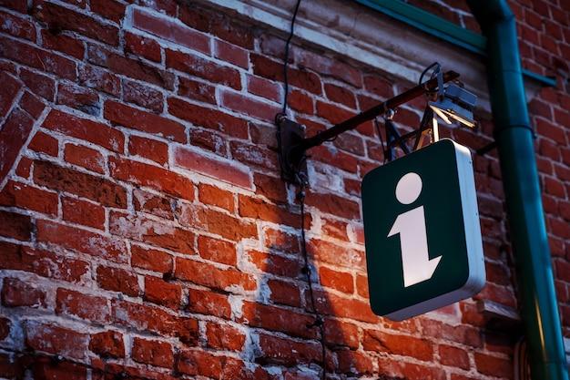 Znak informacyjny, świetlna kostka na starożytnym budynku. znak turystyczny, symbol.