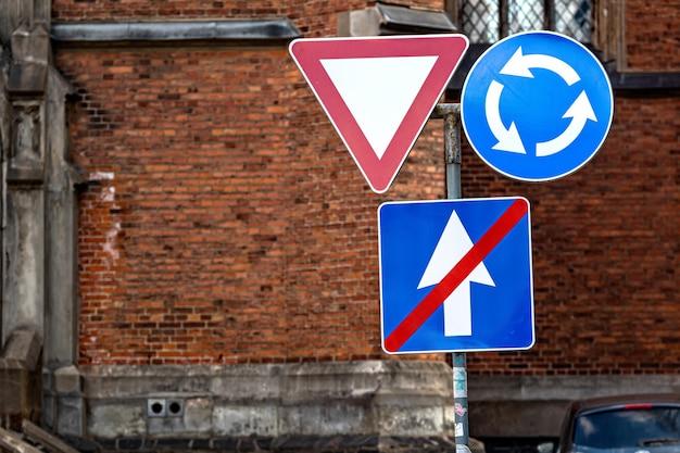 Znak jest ruchem okrężnym, ustępuje i kończy jednokierunkową drogę na tle budynku
