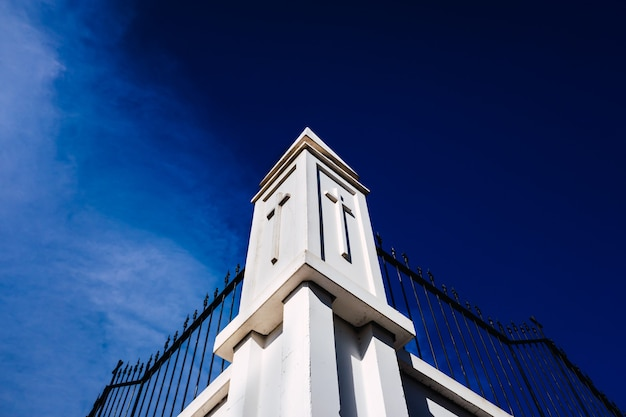 Znak krzyża wyryty na białych ścianach cmentarza.