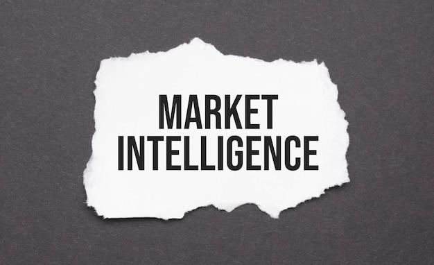 Znak market intelligence na rozdartym papierze