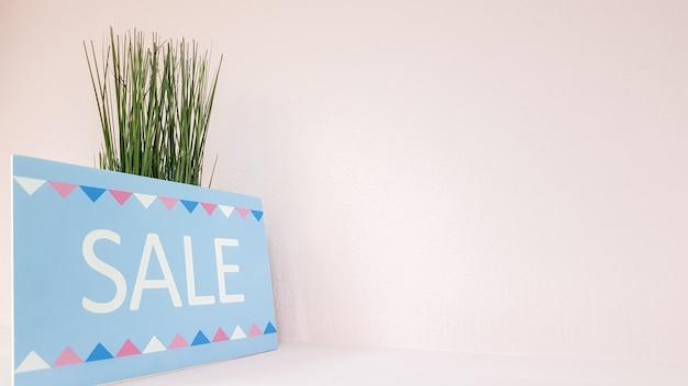 Znak na półce z napisem rabat na tle bladoróżowej ściany z zieloną rośliną w sklepie z odzieżą damską. sprzedaż tabliczek znamionowych. rabat w butiku centrum handlowego.
