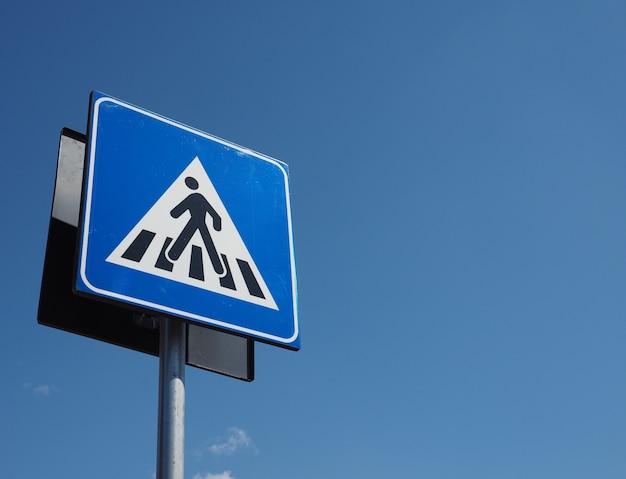 Znak na przejściu zebry nad błękitnym niebem