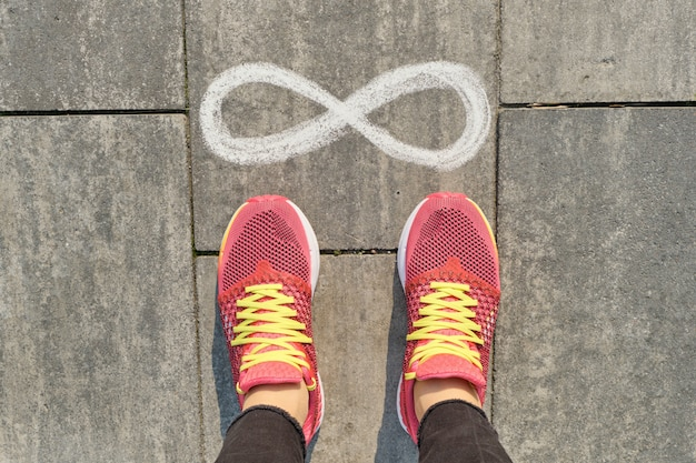 Znak nieskończoności na szarym chodniku z nogami kobiety w trampki