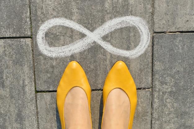Znak nieskończoności na szarym chodniku z nogami kobiety, widok z góry
