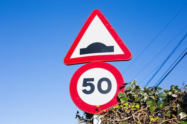 Znak ograniczenia prędkości na zielonych liściach