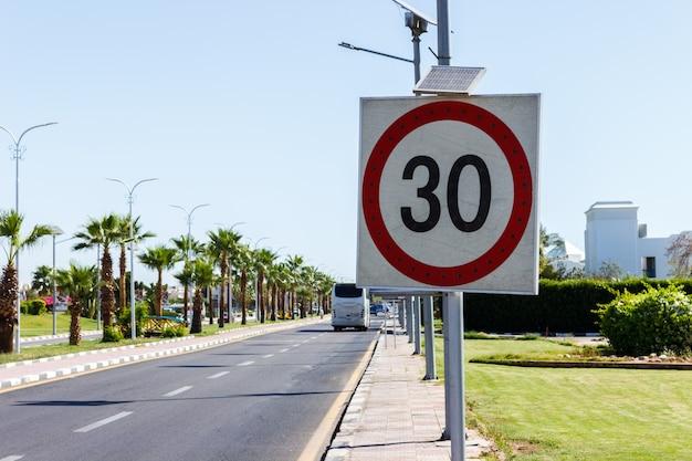 Znak ograniczenia prędkości z panelu słonecznego na drodze z palmy w letni dzień.