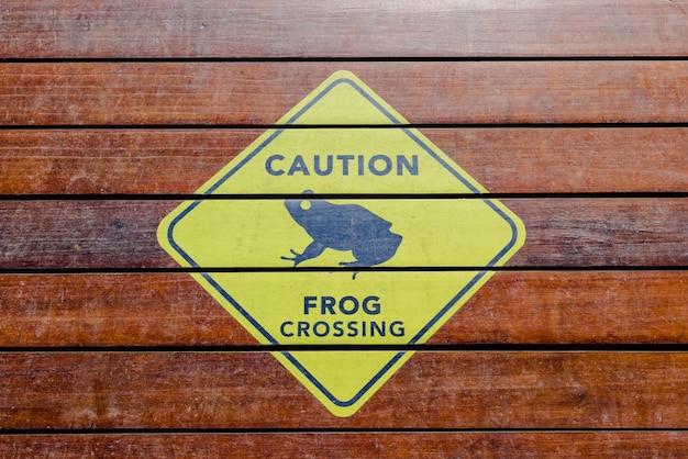 Znak ostrzegawczy, krzyżujące się żaby, malowane na drewnianym moście.