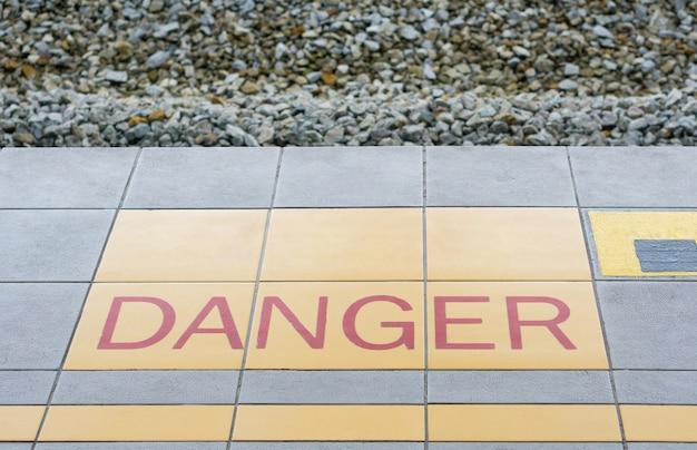Znak ostrzegawczy na niebezpieczeństwo na podłodze pociągu.
