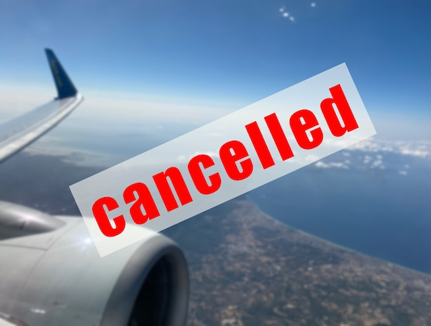 Znak ostrzegawczy o odwołaniu lotu na nieostrym tle lecącego samolotu.