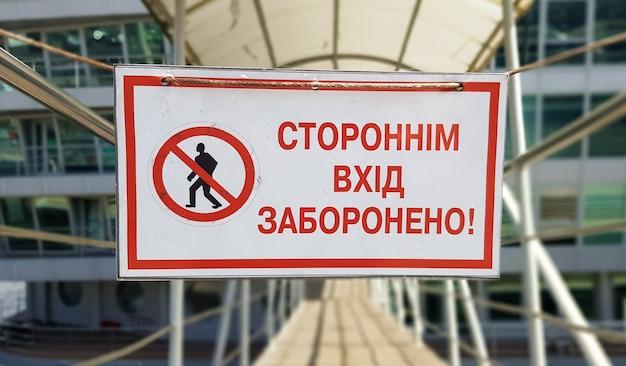 Znak ostrzegawczy zakaz nieautoryzowanego wejścia napisany czerwonym tekstem w języku ukraińskim na białym prostokątnym stole. znak zabrania przejścia nieznajomym.