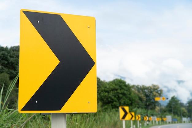 Znak ostrzegawczy zakrętu na drodze.