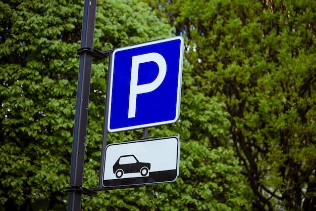 Znak parkingowy dla samochodów na naturalnym zielonym tle drzew