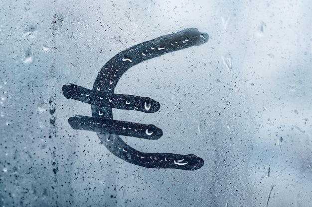 Znak pieniędzy euro na zamglonym oknie z bliska
