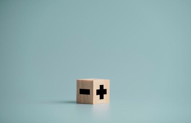 Znak plus i minus po przeciwnej stronie, który drukuje ekran na drewnianym bloku kostki i kopiuje przestrzeń, koncepcja wyboru pozytywnego nastawienia.