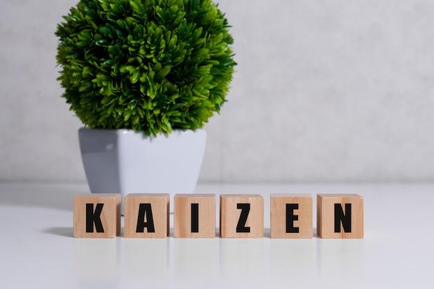 Znak poprawy kaizen wykonany z klocków na drewnianym biurku w jasnym pomieszczeniu.