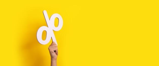 Znak procentu w ręce na żółtym tle, obraz panoramiczny