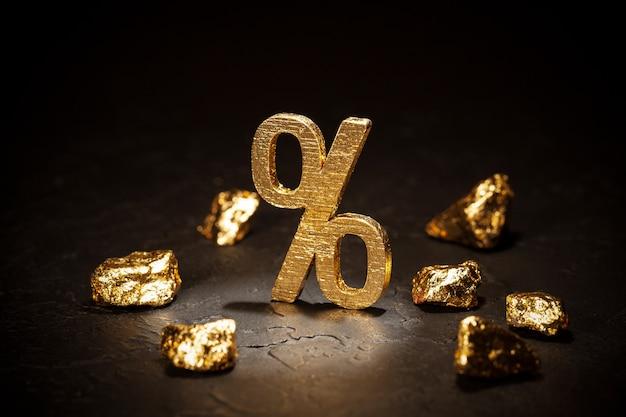 Znak procentu złota i bryłki złota na czarnym tle.
