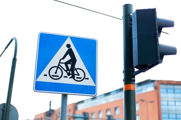 Znak przejazdu rowerowego obok sygnalizacji świetlnej.