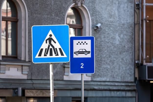 Znak przejścia dla pieszych i parkingu dla taksówek na tle budynku, zbliżenie