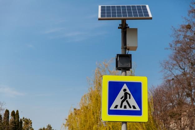 Znak przejścia dla pieszych zasilany panelami słonecznymi zainstalowanymi nad znakami drogowymi i zasadami