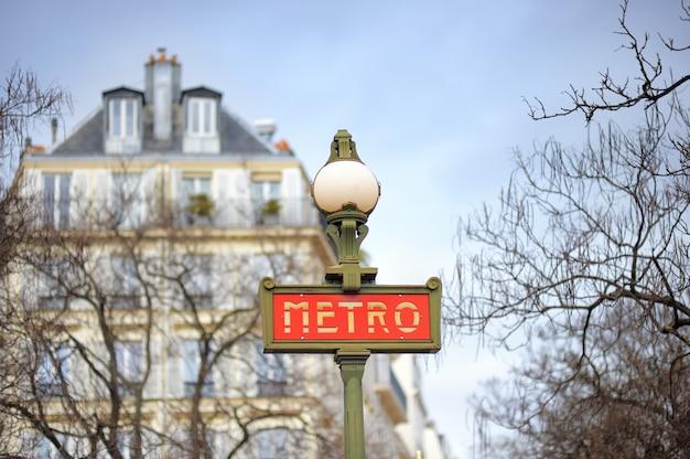 Znak przy wejściu do paryskiego metra z ulicy w tle