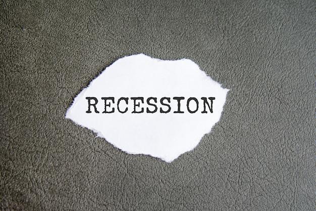 Znak recesji na rozdartym papierze na szarym tle, koncepcja biznesowa