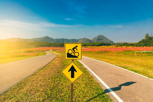 Znak rowerów do stromej drogi z pasmem górskim i niebieskim tle nieba.