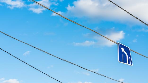 Znak skrętu w lewo wiszący na drucie na tle błękitnego nieba