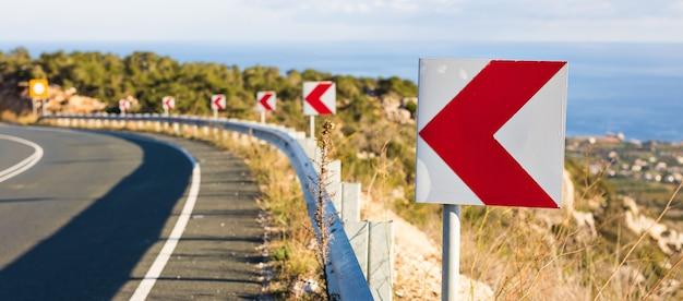 Znak skrętu w lewo: znaki drogowe ostrzegają przed ostrym zakrętem na wąskiej drodze.