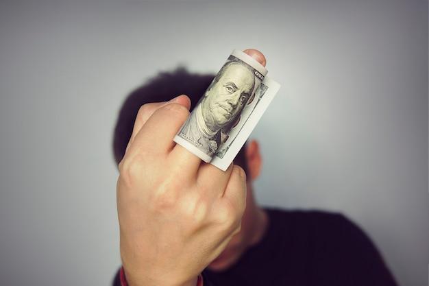Znak środkowy palec pieniądze stu dolarów rachunek człowieka w czarnym t-shirt neutralnym szarym tle. pogarda dla pieniędzy, korupcja, sprzedajność, przekupstwo, przekupstwo