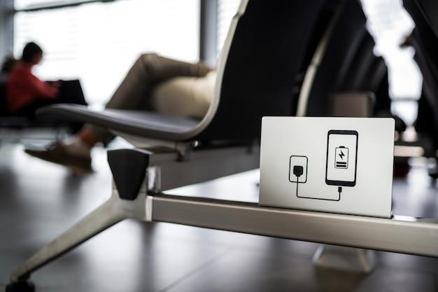 Znak stacji ładowania smartfonów na krzesłach oczekujących na lotnisku.