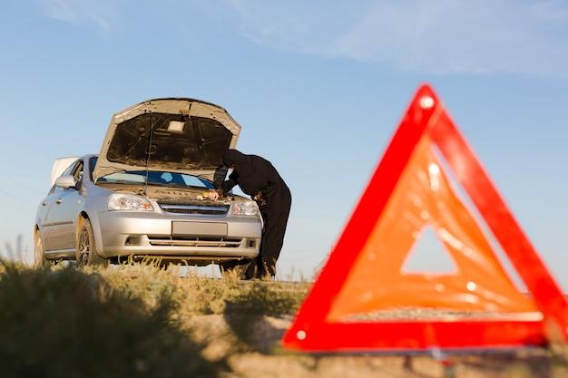 Znak stopu awaryjnego i auto naprawa kobieta kierowca muzułmański.
