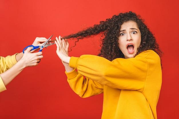 Znak stopu. obraz krzyczącej młodej dziewczyny z kręconymi włosami i fryzjera próbującego ściąć sobie włosy.