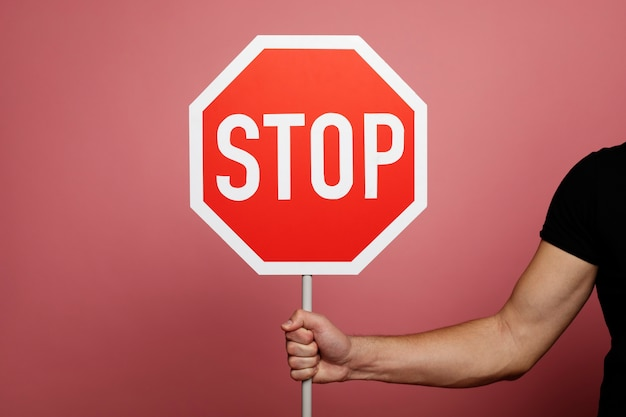 Znak stopu. zatrzymać znak drogowy w dłoni mężczyzny.